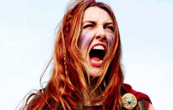 Caucasian Woman with red hair, and war paint, in the middle of a shout. Representing women's voice online.
